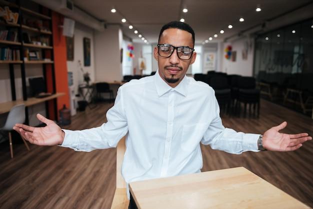 Красивый бизнесмен в очках сидит за столом и смотрит вперед