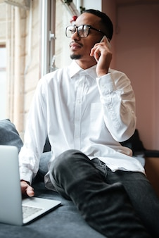 Handsome businessman wearing glasses sitting near window and typing by laptop computer while talking by phone