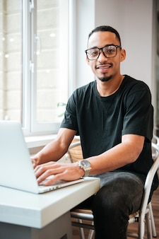 Handsome businessman wearing glasses sitting near window and typing by laptop computer