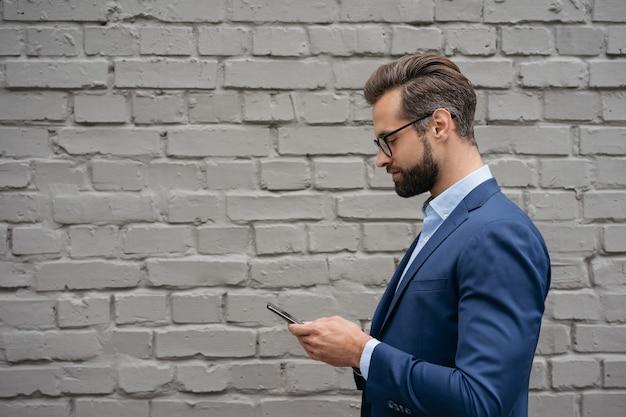 オンラインで携帯電話通信を保持しているスーツとスタイリッシュな眼鏡を身に着けているハンサムなビジネスマン