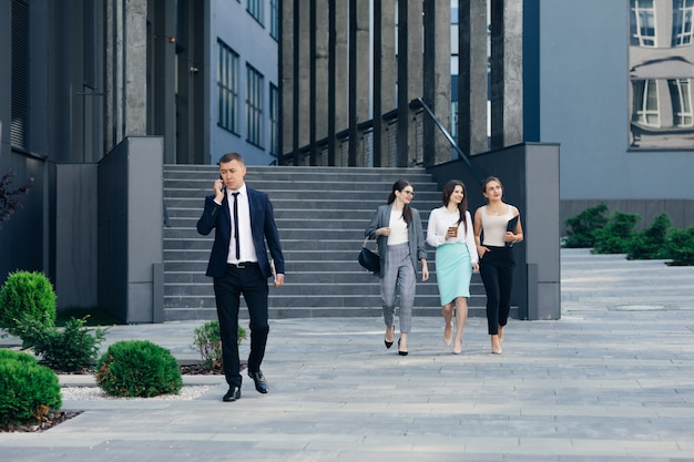 Handsome businessman wearing suit talking on the phone walking near bussiness centre. successful business. wearing classical suit. social network. apps. smartphones.