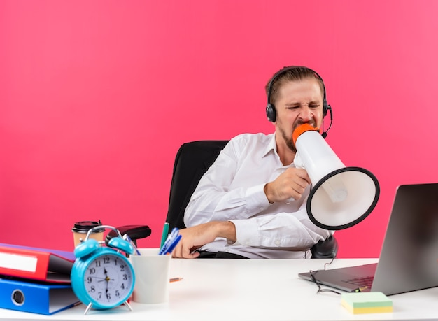 Handsome businessman in white shirt and headphones with a microphone shouting to megaphone with aggressive expression sitting at the table in offise over pink background