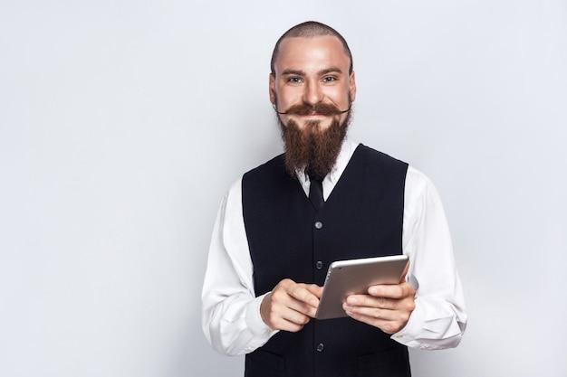 수염과 핸들 콧수염이 디지털 태블릿을 들고 웃는 얼굴로 카메라를 바라보는 잘생긴 사업가. 스튜디오 촬영, 회색 배경입니다.