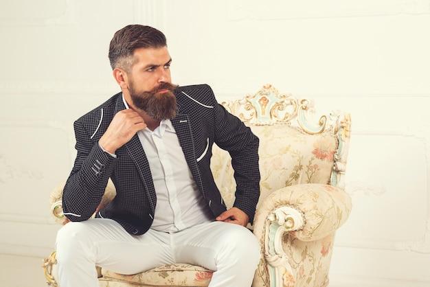 Красивый бизнесмен с бородой в черном костюме, сидя на стуле. впечатляющий хорошо одетый бородатый мужчина сидит в кресле в роскошных апартаментах с классическим интерьером. роскошь. мужская красота, мода.