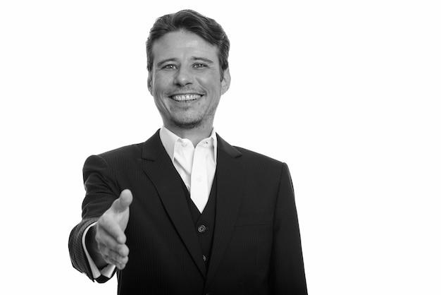 黒と白の白い壁に対して分離されたスーツのひげの無精ひげを持つハンサムなビジネスマン