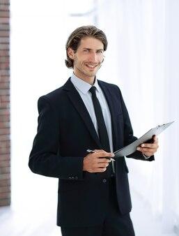 Красивый бизнесмен с бизнес-документом, стоящим в офисе