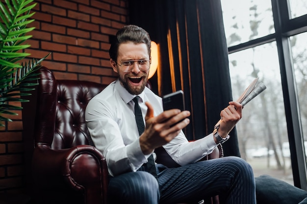 Handsome businessman with candid emotions holding his smartphone and newspaper while sitting on armchair.