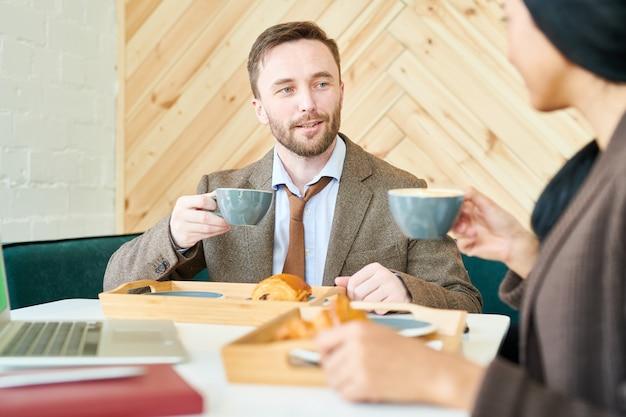 カフェでのコーヒーのカップを持つハンサムな実業家