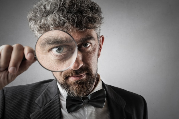Handsome businessman with magnifying glass