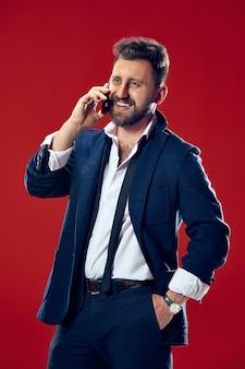 Uomo d'affari bello con il telefono cellulare. uomo d'affari felice in piedi isolato su sfondo rosso studio. bellissimo ritratto maschile a mezzo busto
