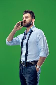 휴대 전화와 잘 생긴 사업가입니다. 녹색 스튜디오 배경에 고립 된 서 심각한 비즈니스 남자