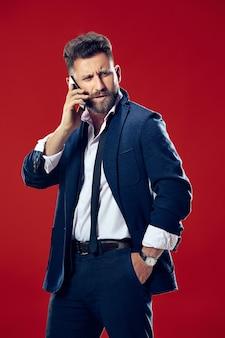 휴대 전화와 잘 생긴 사업가입니다. 빨간 스튜디오 배경에 고립 된 서 심각한 비즈니스 사람. 아름다운 남성 반장 초상화. 인간의 감정, 표정 개념.