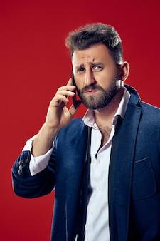 Uomo d'affari bello con il telefono cellulare. uomo serio di affari che sta isolato sulla parete rossa. bellissimo ritratto maschile a mezzo busto. emozioni umane, concetto di espressione facciale.