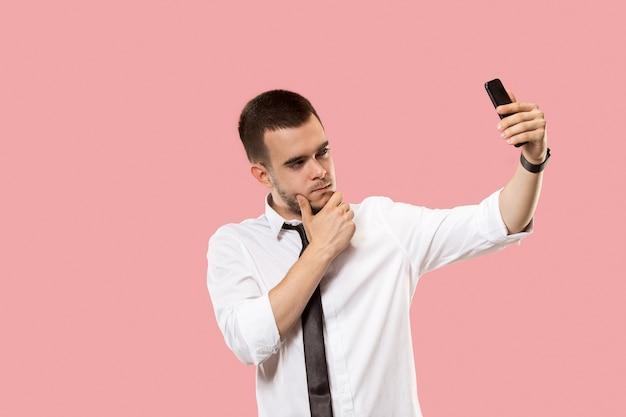 携帯電話を持つハンサムなビジネスマン。ピンクのスタジオの背景に分離された自分撮り写真を立って作っている若いビジネスマン。