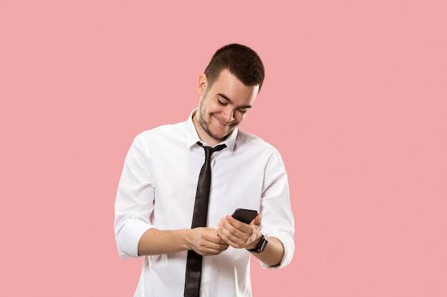 携帯電話を持つハンサムなビジネスマン。ピンクに孤立して立っている若いビジネスマン。美しい男性の半身像
