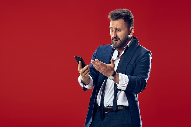 携帯電話を持つハンサムなビジネスマン