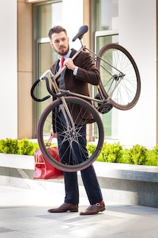 Handsome businessman with a red bag carrying his bicycle on city streets.