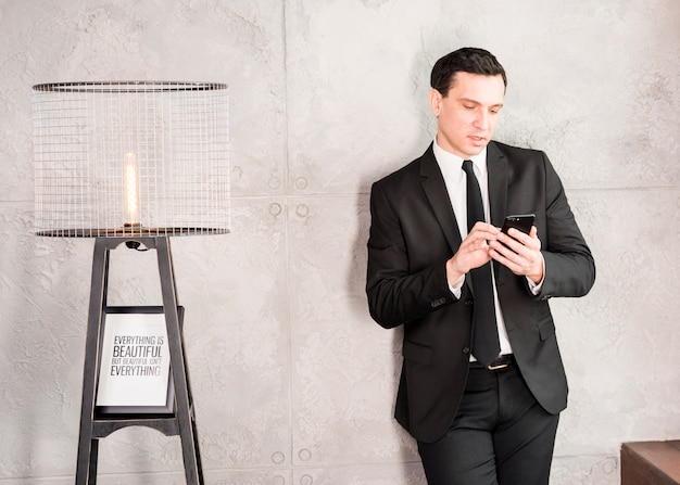 Handsome businessman with smartphone leaning on wall