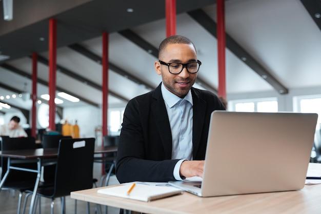 Красивый бизнесмен, работающий и использующий ноутбук в офисе