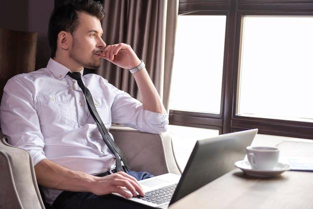 Handsome businessman working at laptop in restaurant.