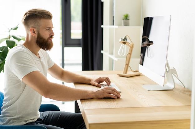 Красивый бизнесмен, работающий на компьютере в офисе.