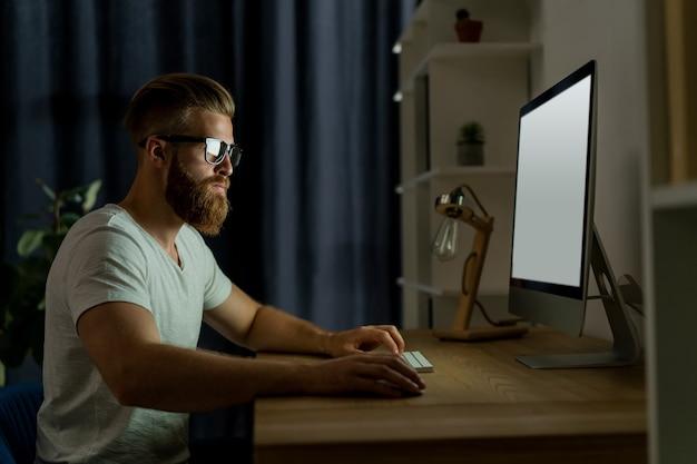 オフィスでコンピューターに取り組んでいるハンサムなビジネスマン。