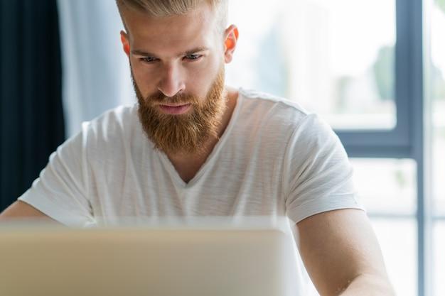 Красивый бизнесмен, работающий с ноутбуком в офисе.