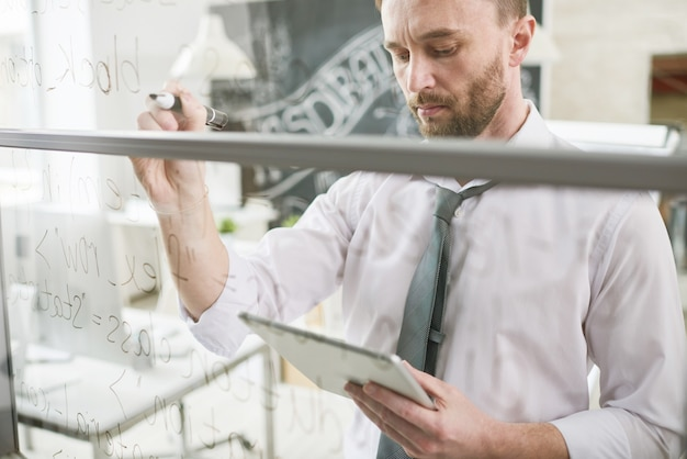 Handsome businessman writing on glass wall