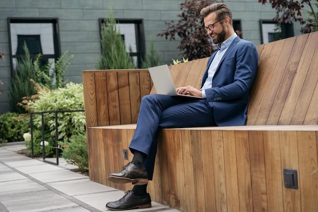 Красивый бизнесмен наблюдает за учебными курсами фрилансер с помощью ноутбука, работающего в интернете