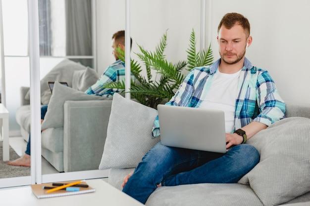 Красивый занятый сосредоточенный мужчина в рубашке расслабленно сидит на диване у себя дома за столом, работая онлайн на ноутбуке из дома