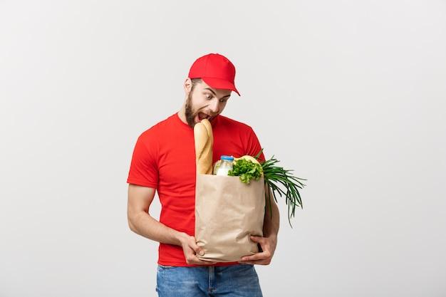 食料品の食べ物や飲み物のパッケージバッグを運ぶハンサムな白人配達人