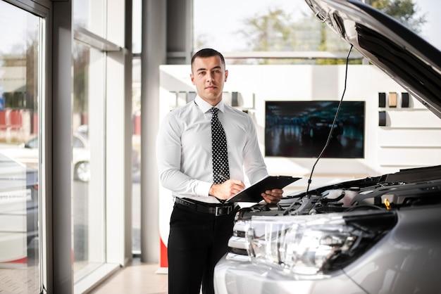 Commerciante di automobile bello che tiene una lavagna per appunti