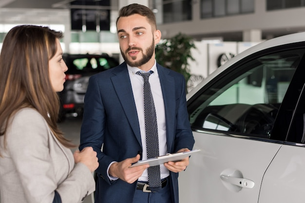 Handsome car salesman consulting client