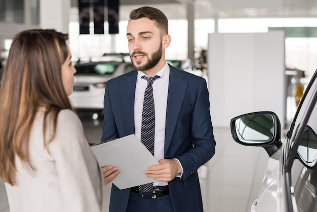 Handsome car salesman consulting woman