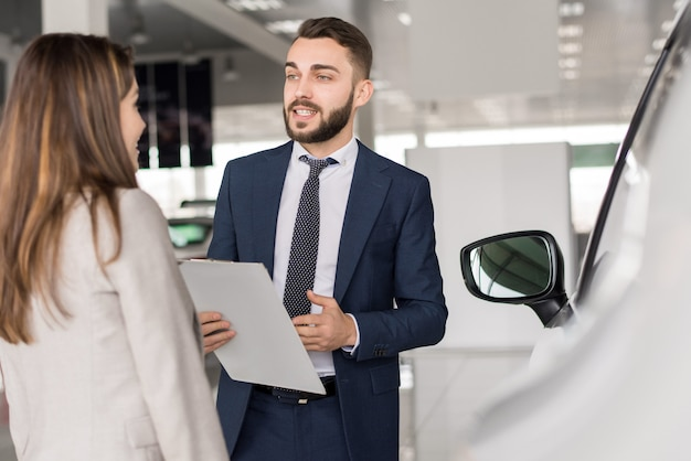 Handsome car salesman selling cars
