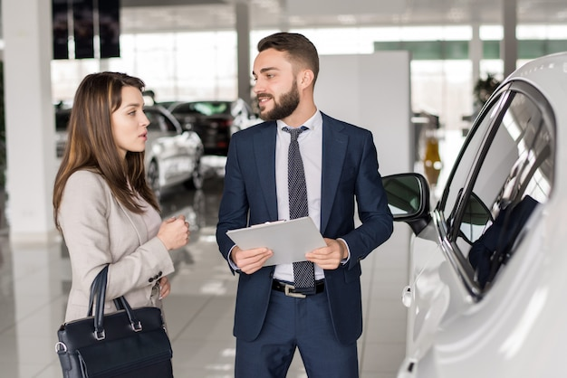 Красивый продавец автомобилей разговаривает с клиентом