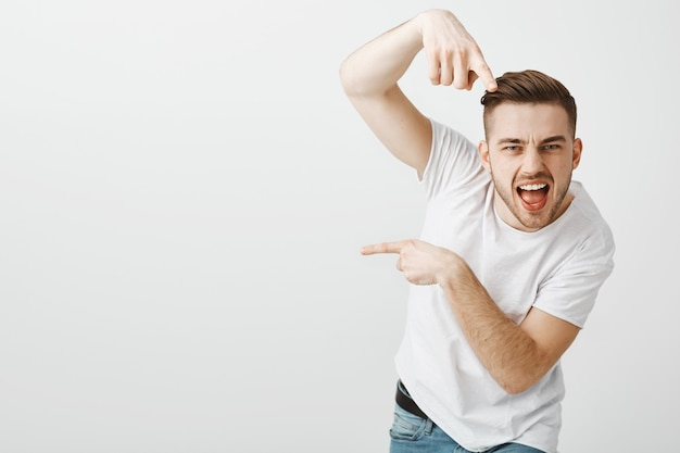 ハンサムな屈託のない男がヒップホップを踊り、左を指す