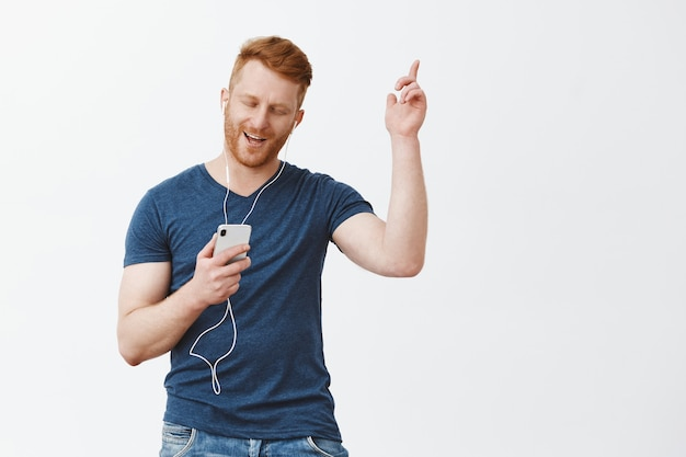 Handsome carefree and joyful modern bearded male in blue t-shirt raising hand in dance move, holding smartphone, listening songs in earphones