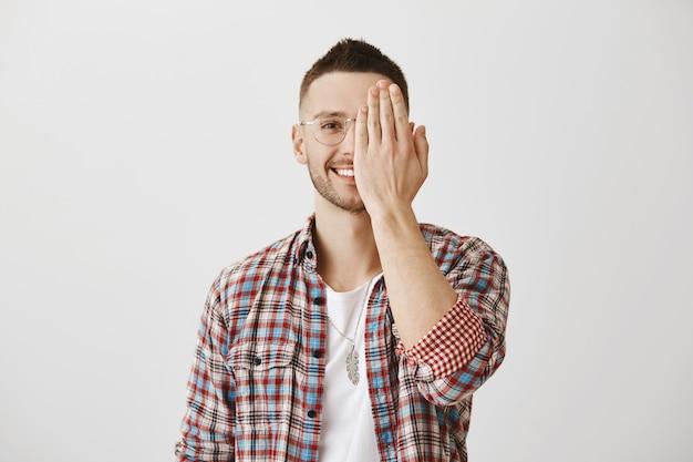 Красивый беззаботный молодой парень в очках позирует