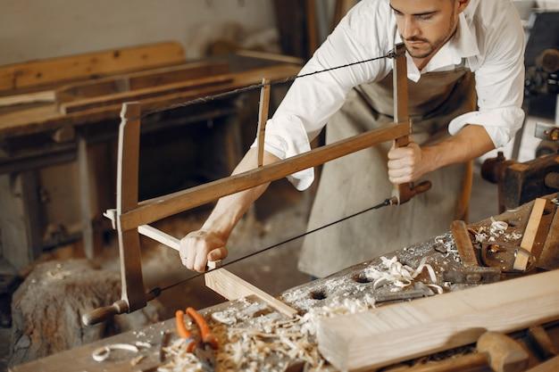 Carpentiere bello che lavora con un legno