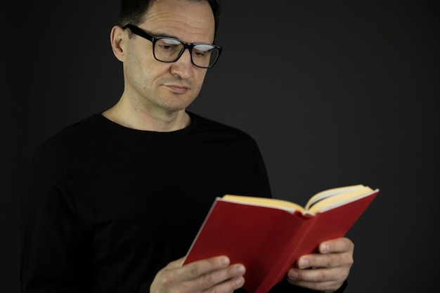 ハンサムなカジュアルな服を着てメガネで黒い髪の40代の男が密接に赤い本を読みます