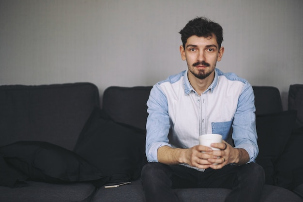 Handsome casual man sitting on couch having coffee