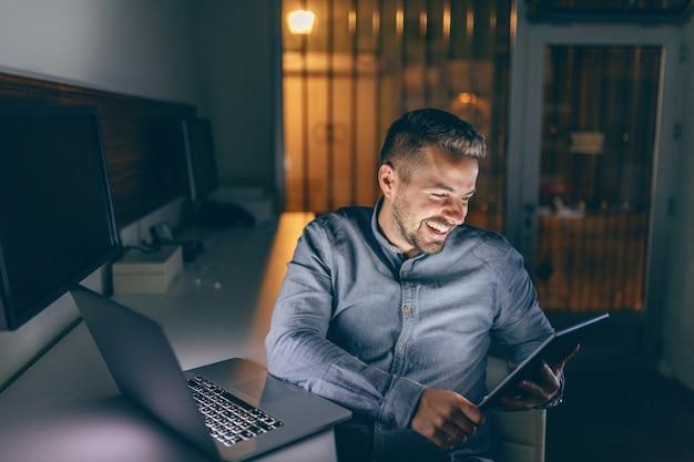 ハンサムな白人のひげを生やした笑顔でこぼれるような笑顔で夜遅くまでオフィスに座っているとタブレットを使用しています。