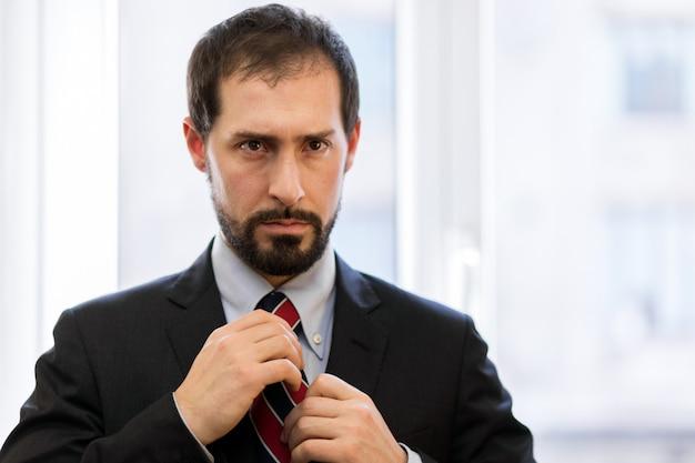 Handsome caucasian businessman adjusting his collar