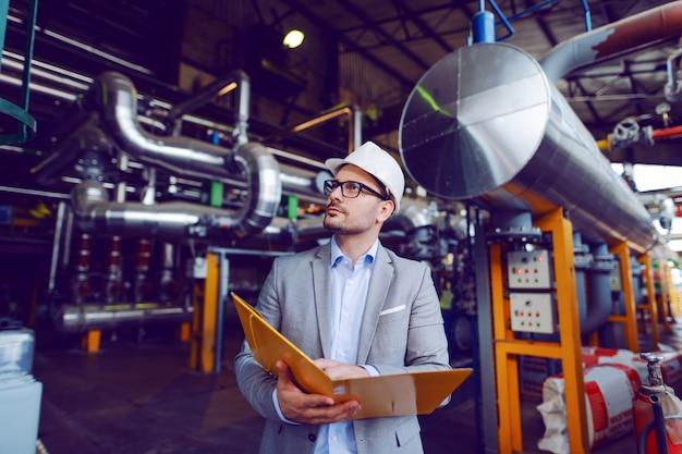 Красивый кавказский бизнесмен в костюме и с защитным шлемом на голове держа папку с документами пока стоящ в электростанции.