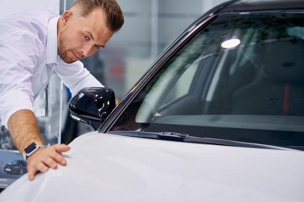 ハンサムな白人ビジネスマンはそれを購入する前に車を調べています