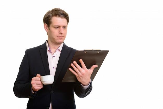 Cを押しながらクリップボードを読んでハンサムな白人実業家