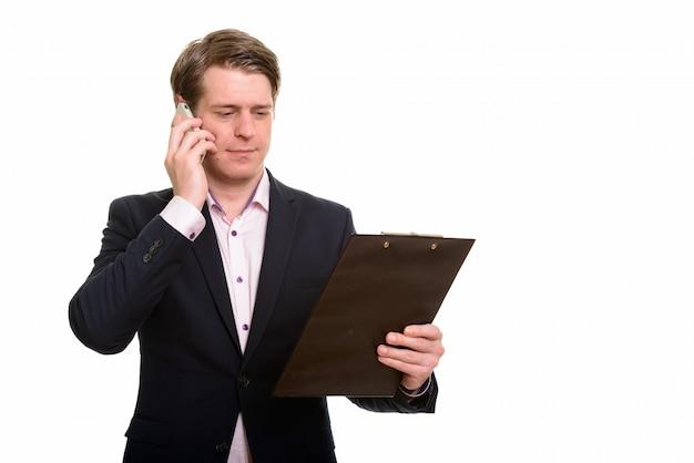 Oを話しながらクリップボードを読んでハンサムな白人実業家
