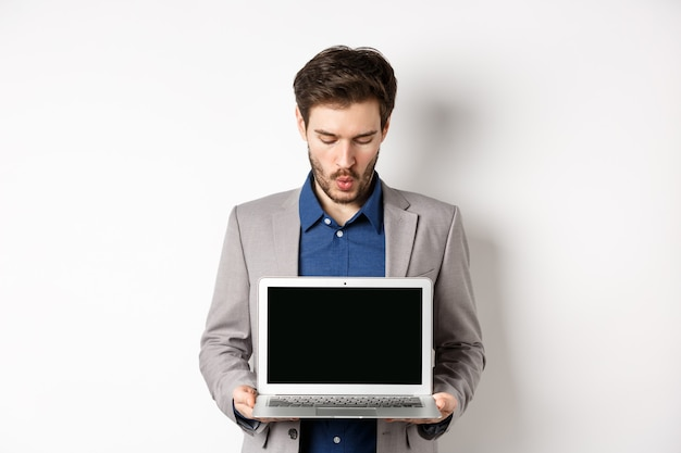 Handsome caucasian businessman in suit showing empty laptop screen, demonstrate promo