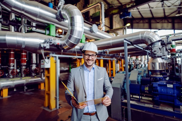 Handsome caucasian businessman in suit and with protective helmet on head holding folder with documents while standing in power plant.